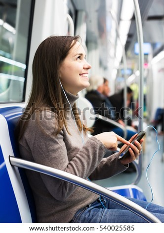Young smiling woman playing with mobile phone at subway car