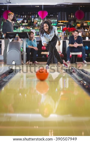 young smiling woman plays bowling with her friends - stock photo