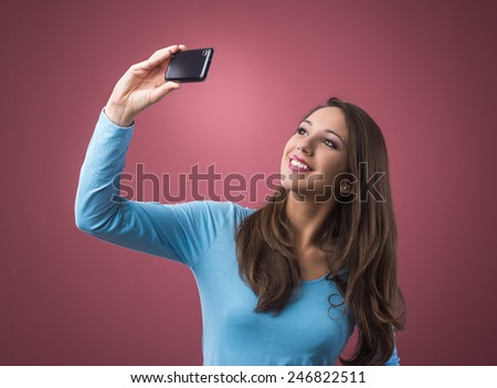 Young smiling woman posing and taking self portraits with her smart phone - stock photo