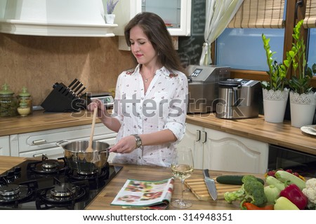 Young smiling woman preparing food and cooking in her kitchen.