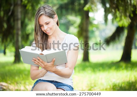 Young smiling woman reading a book while sitting in the park