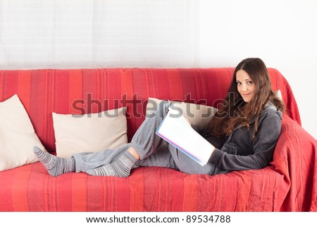 Young smiling woman reading a magazine on a red sofa - stock photo