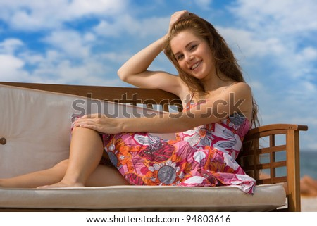 young smiling woman relaxing on natural background - stock photo