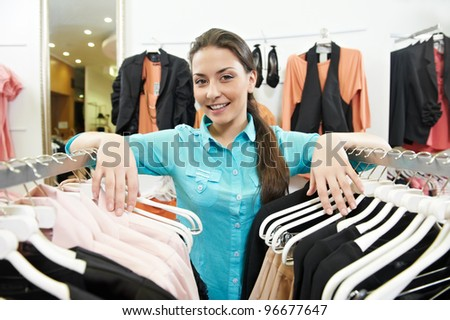 Young smiling woman seller assistant with hands on clothing hangers at shopping store - stock photo