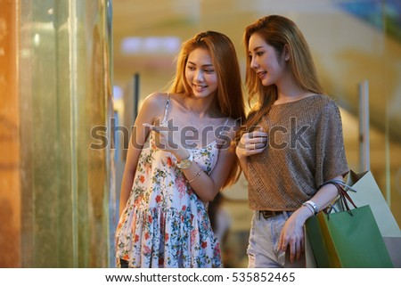 Young smiling woman showing clothes in showcase to her sister