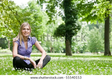 Young smiling woman siting in grass with flowers - outdoors scene