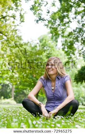 Young smiling woman siting in grass with flowers - outdoors scene - stock photo