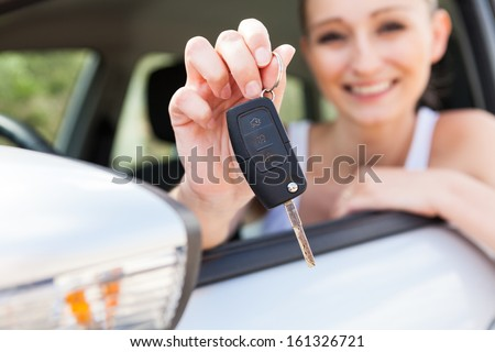 young smiling woman sitting in car taking key handover rent  purchase - stock photo