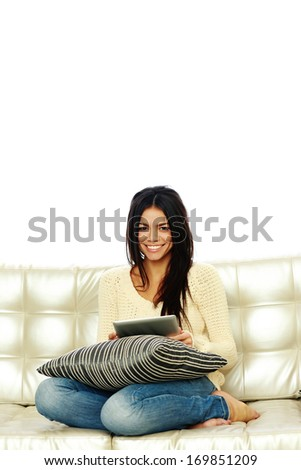 Young smiling woman sitting on the sofa with tablet computer and looking at camera - stock photo