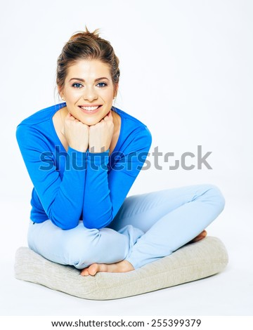 Young smiling woman sitting pose portrait. Yoga lotus pose of beautiful girl. Casual home style. - stock photo