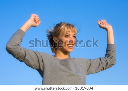 Young smiling woman spreading arms to  blue sky