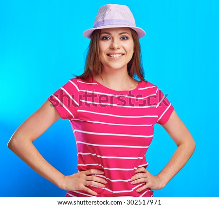 Young smiling woman standing against blue background. isolated studio portrait.