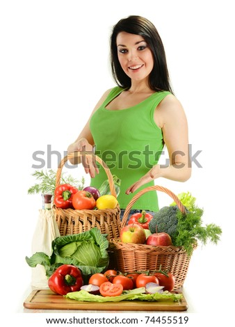 Young smiling woman standing at the table with variety of fresh raw vegetables in wicker baskets isolated on white - stock photo