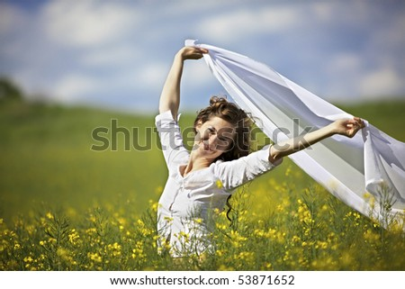 Young smiling woman standing in yellow rapeseed field holding a white long piece of cloth in the wind. - stock photo