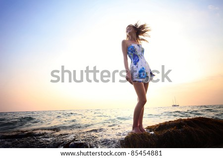 Young smiling woman standing on a rock near sea holding her dress and looking to a horizon - stock photo