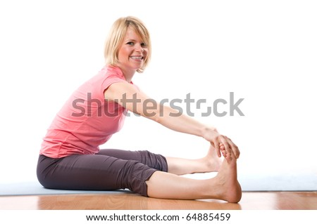 Young smiling woman stretching holding her feet - stock photo
