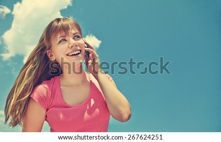 young smiling woman talking on mobile phone on blue sky background. girl with a smartphone - stock photo