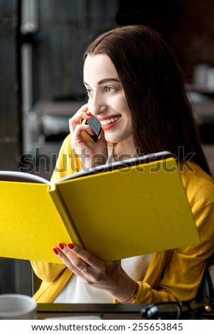 Young smiling woman talking with phone while holding yellow book in the dark interior
