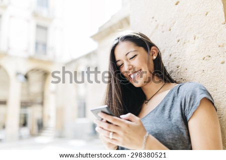 Young smiling woman text messaging on mobile phone - stock photo