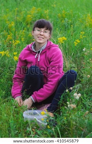 young smiling woman to picking wild strawberries - stock photo