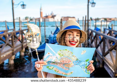 Young smiling woman traveling with paper map and venetian mask standing near San Marco square with gondolas on the background in Venice. - stock photo