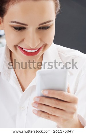 Young smiling woman using mobile phone.