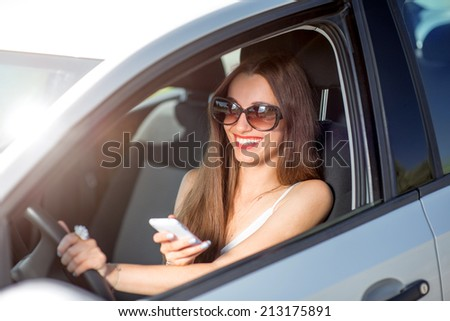 Young smiling woman using phone while driving her car - stock photo