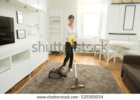 Young smiling woman vacuum cleaning carpet stock photo for Modern cleaning concept