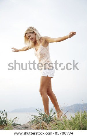 young smiling woman walking on a sand dune on the beach - stock photo