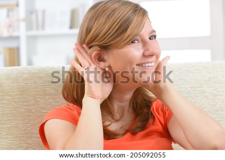 Young, smiling woman wearing deaf aid - stock photo