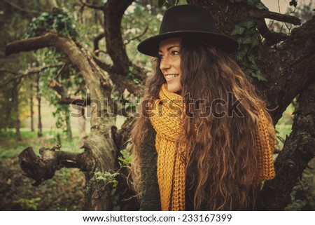 young smiling woman wearing hat, yellow wool csarf and green dress  in park  autumn winter fashion - stock photo