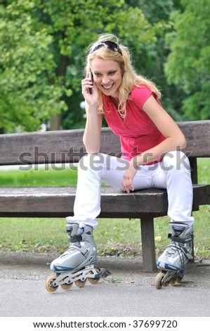 Young smiling woman wearing rollerblades calling with mobilephone outdoors
