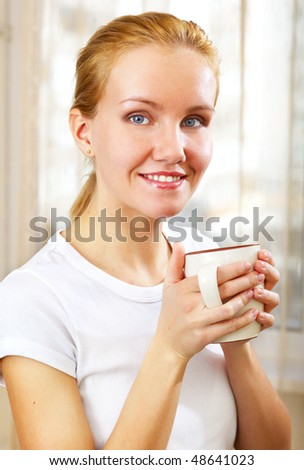 young smiling woman with a cup at home - stock photo