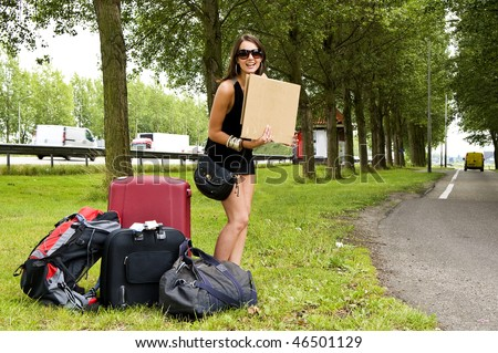 Young, smiling, woman, with a lot of luggage, trying to hitch a ride on a resting place along a busy highway - stock photo