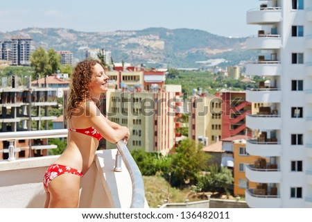 Young smiling woman with closed eyes stands on balcony with her face to sun - stock photo
