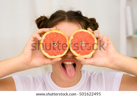 Young smiling woman with grapefruit making funny face