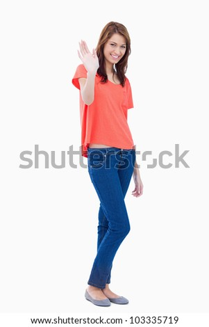 Young smiling woman with her hand raised as a greeting - stock photo