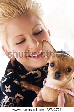 Young smiling woman with her little chihuahua. Focus on woman. - stock photo
