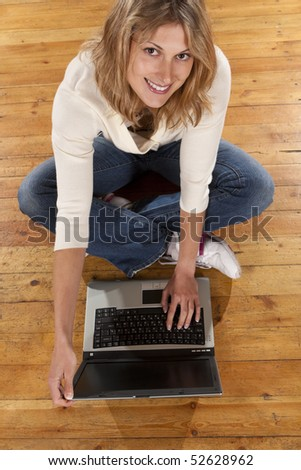 Young smiling woman with laptop computer. Top view - stock photo