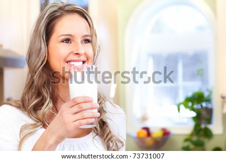 Young smiling woman with milk at home
