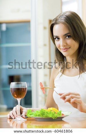 Young smiling woman with salad and redwine at home