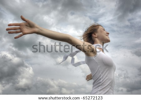 Young smiling woman with white ribbon and raised hands on clouds background - stock photo
