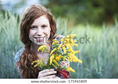 Young smiling woman with yellow flowers in front of a field