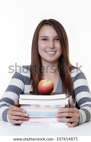 young smiling woman working at her desk with a pile of books and a apple for snack time to keep her going - stock photo