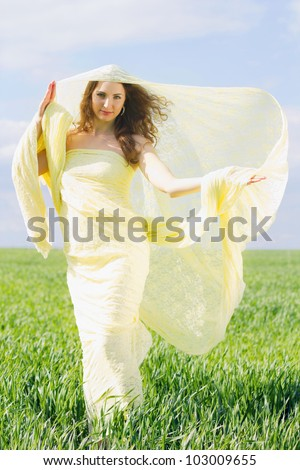 Young smiling woman wrapped in yellow cloth - stock photo