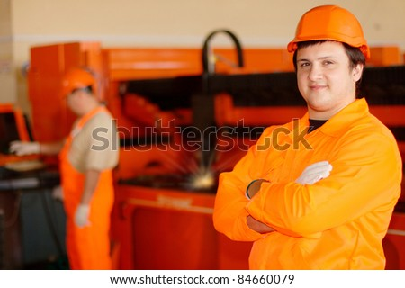 Young smiling worker with a laser at the background - stock photo