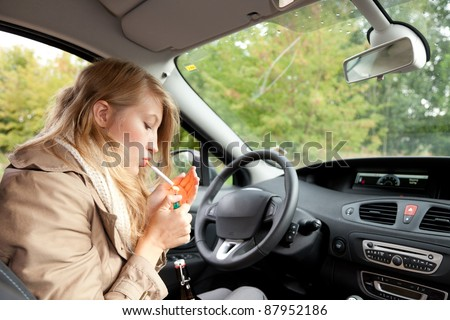 young smoking woman driving her new car - stock photo