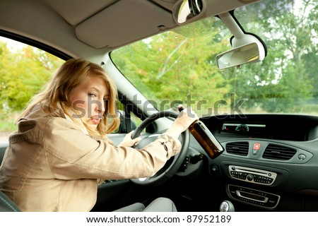 young smoking woman driving her new car