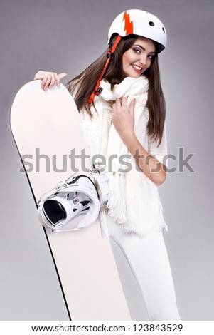 young snowboarder girl in winter clothing with snowboard in her hands - stock photo