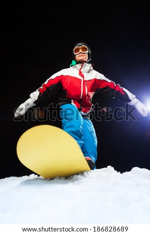 Young snowboarder wearing ski mask ready to slide - stock photo